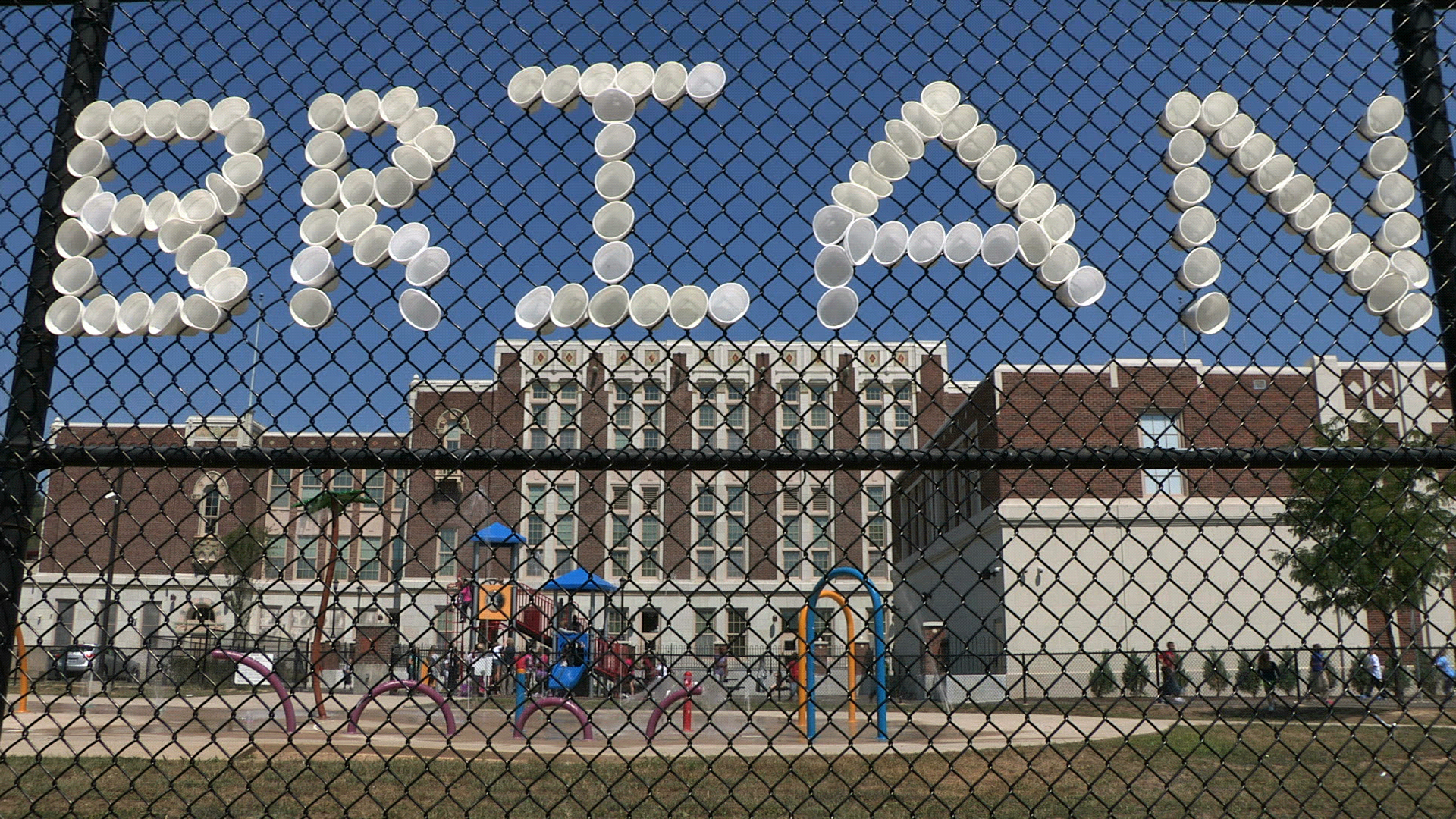 A memorial of Styrofoam cups pays tribute to Brian Thompson, 27, who was murdered across the street from the school in the summer of 2012. Thompson was an Oyler parent who had attended the school as a child. When the new Oyler School reopened later that summer, Hockenberry hoped its presence would help slow the crime in the neighborhood. Photo by Glenn Hartong. © 2013, Amy Scott.