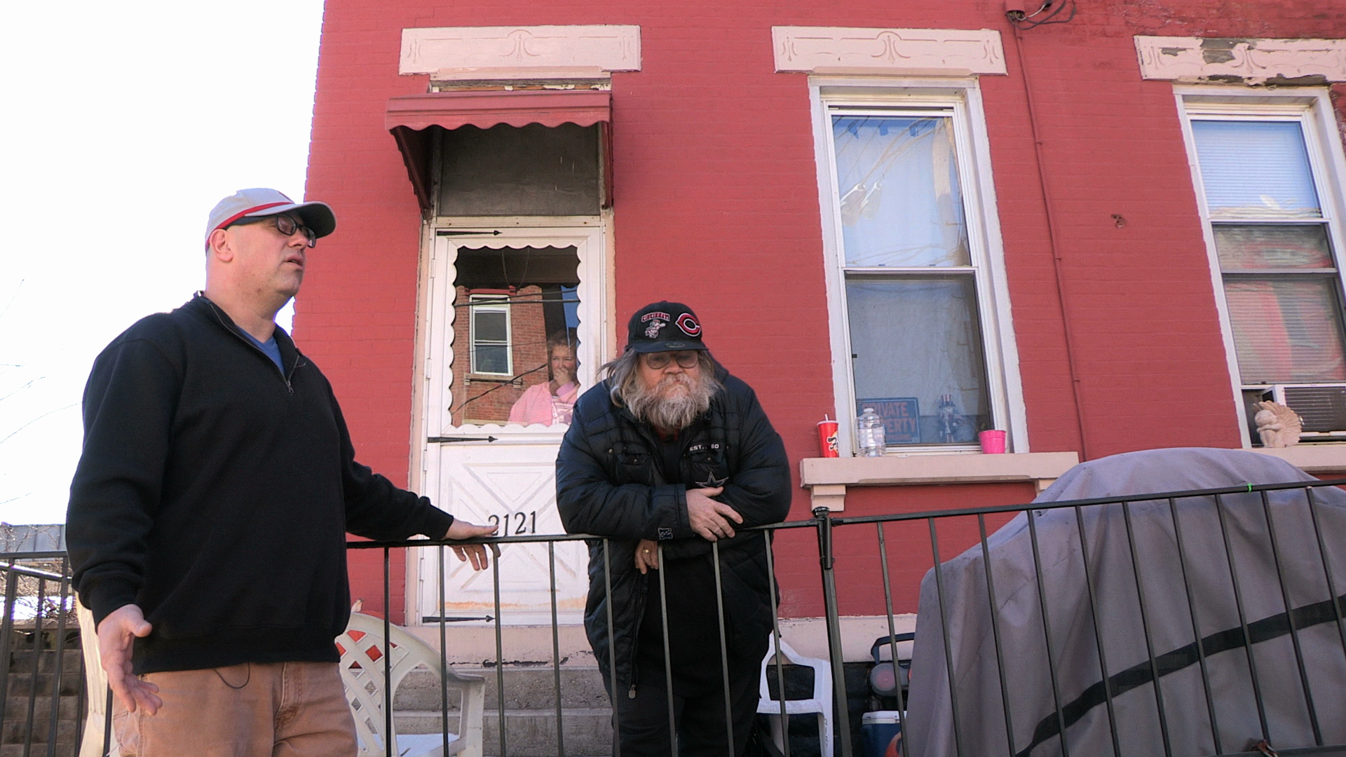 "Friends Joe Saylor (left) and Gary Thomas talk in front of Thomas's house in Lower Price Hill. Thomas has lived in the neighborhood for more than fifty years and volunteers at Oyler School. ""You always seem to find somebody who you can lean on and talk to,"" he says of the close-knit community. Saylor grew up a block away from Oyler and was a student there. Now he teaches at the school. Photo by Glenn Hartong. © 2013, Amy Scott."