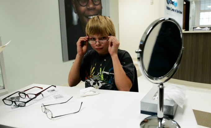 "Timothy Drifmeyer, age 13, tries on glasses at the OneSight Vision Center inside Oyler School. Opened in 2012, the center provides free eye exams and glasses to children throughout the school district. Established through philanthropy, the clinic sustains itself by billing Medicaid or, if a family has it, private insurance. Before the clinic opened, around 140 kids at Oyler failed a routine eye screening each year, but many went untreated. ""Poverty interferes with children getting health care,"" says Marilyn Crumpton with the Cincinnati Health Department. Photo by Stacy Doose. © 2013, Amy Scott."