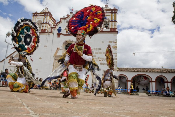 "Dancers in the courtyard in front of the church. Martin's intention was to use the dance justify his rule and to emphasize to indigenous people the uselessness of resistance. But after over 450 years, the dance no longer means what it once did. If anything, it represents a spirit of resistance to those forces that would deny Zapotecs their language, dance, music, and other cultural traditions. The Dance of the Feather is one element of a broader indigenous culture maintained through hundreds of years of colonization, followed by decades of official national policies denying their culture's autonomy and value. Hernandez says, ""The Dance of the Feather keeps its importance in communities that hold to the tradition, like Teotitlan del Valle, because it fulfills the function of reaffirming their cultural identity by recalling a glorious past, that is, of what the community was before the arrival of the Spanish, and what it continues to be in spite of them. The Dance prevents forgetting, because it recalls the struggle that native Zapotecs maintained with the Spanish to defend their territory, and from whom they inherited, according to the perception of the townspeople, only negative things."""