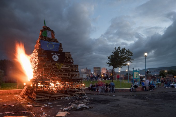 Belfast's extended twilight makes for some spectacular scenes. This children's bonfire is dressed with two Irish tricolors, the European Union flag, the Isis flag, and a jersey from the Celtic Football Club.