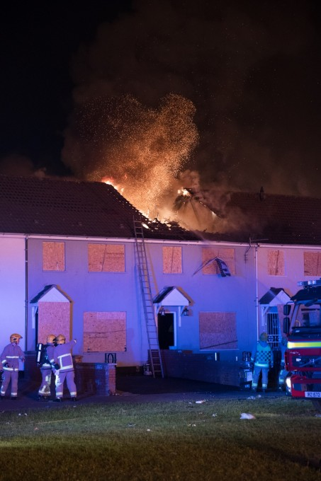 Despite boarding up windows and doors to protect houses from the Shankill bonfire's spectacular embers, the roof of a nearby row house ignited, destroying multiple units. This is the moment the first roof collapsed.