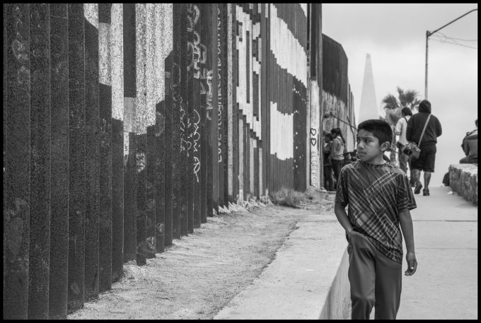 A boy walks past the Mexican side of the border wall. Copyright David Bacon
