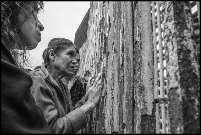 In Playas de Tijuana, on the Mexican side of the border wall, Catelina Cespedes and Carlos Alcaide greet Florita Galvez, who is on the U.S. side. Copyright David Bacon