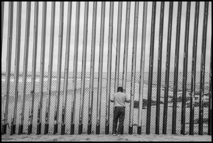 A man looks through the bars of the border wall into the U.S. Copyright David Bacon