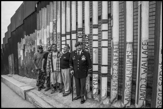 On the Mexican side, veterans of U.S. military service who have been deported gather to protest and remember those who died. Their names are written on the bars. Copyright David Bacon